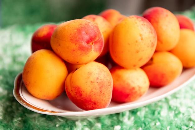 Reife aprikosen in einer platte auf einem grünen hintergrund