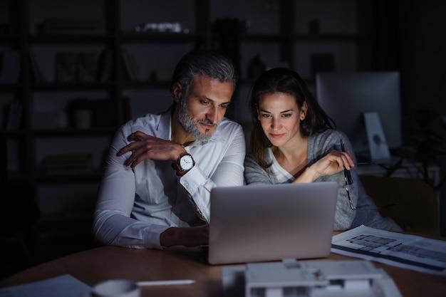 Reife architekten mit laptop am schreibtisch im büro sitzen, spät arbeiten.