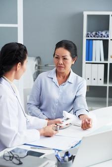 Reife asiatin, die in der arztpraxis sitzt und blutdruck messen lässt