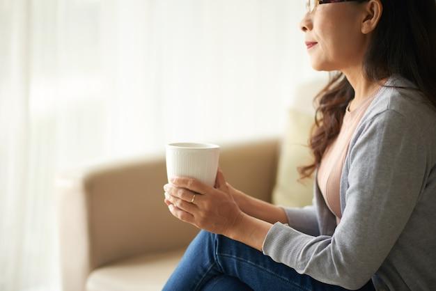 Reife asiatische frau, die sich zu hause mit tasse tee entspannt