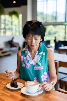 Reife asiatische frau essen schokoladen-brownie-kuchen und einen kaffee in einem café