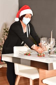 Reife asiatische frau mit einer gesichtsmaske und einer weihnachtsmütze, die zwei gläser auf einen tisch stellt