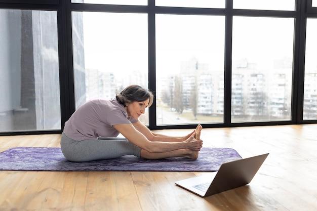 Reife athletische frau macht yoga online zu hause