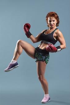 Reife athletische rothaarige frau im sportbekleidungs-t-shirt und in den shorts, die fitnessübungen in boxhandschuhen tun