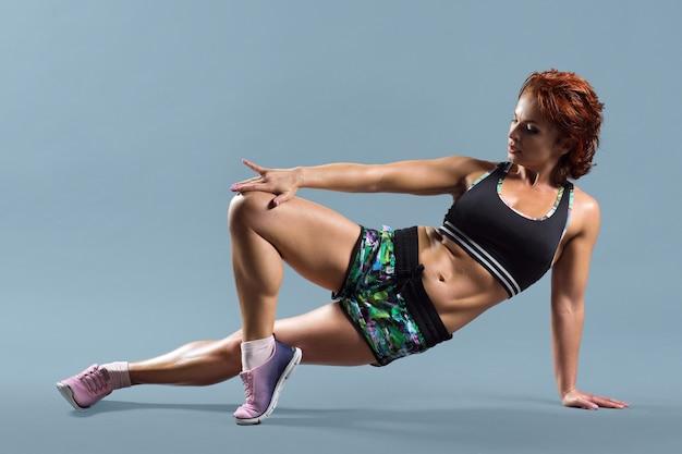 Reife athletische rothaarige frau im sportbekleidungs-t-shirt und in den shorts, die fitnessübungen machen