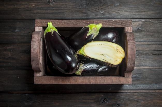 Reife aubergine in der schachtel auf schwarzem holztisch