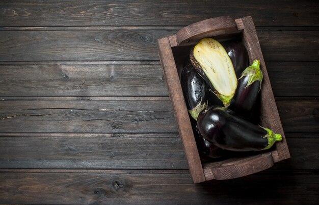 Reife aubergine in der schachtel auf schwarzem rustikalem tisch