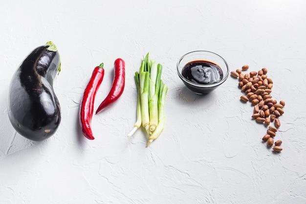 Reife auberginenzutaten zum kochen oder grillen von chili, auberginen, sauce, nüssen auf weiß