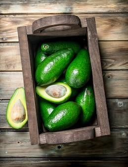 Reife avocado in einer holzkiste. auf einem braunen holz.