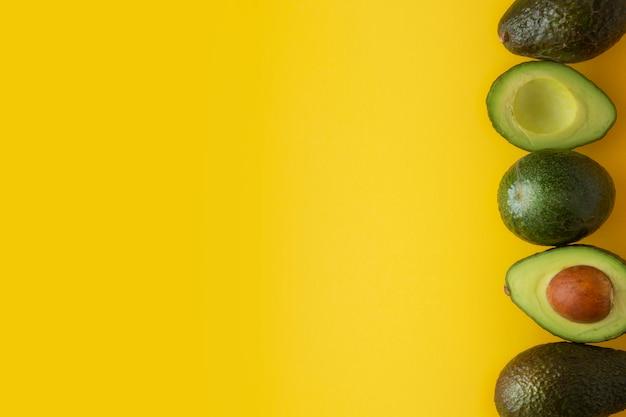 Reife avocado lokalisiert auf gelbem hintergrund. kopieren sie platz.
