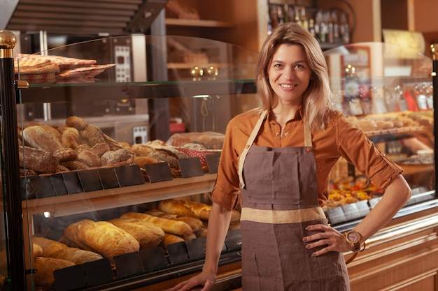 Reife bäckerin, die an ihrem bäckereigeschäft arbeitet