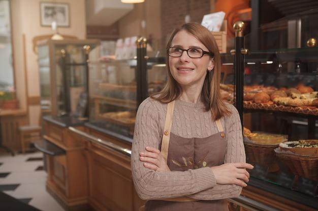 Reife bäckerin, die verträumt wegschaut und in ihrer bäckerei arbeitet