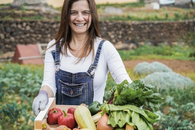 Reife bäuerin, die holzkiste mit frischem bio-gemüse hält - fokus auf gesicht