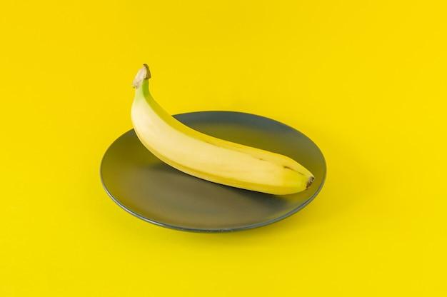 Reife banane auf schwarzem teller auf gelbem hintergrund. tropische früchte zum essen.