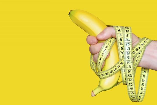 Reife banane in der hand mit einem zentimeterband lokalisiert auf gelbem hintergrund, konzept der fitnessernährung zur gewichtsreduktion, platz für copyspace, nahaufnahme