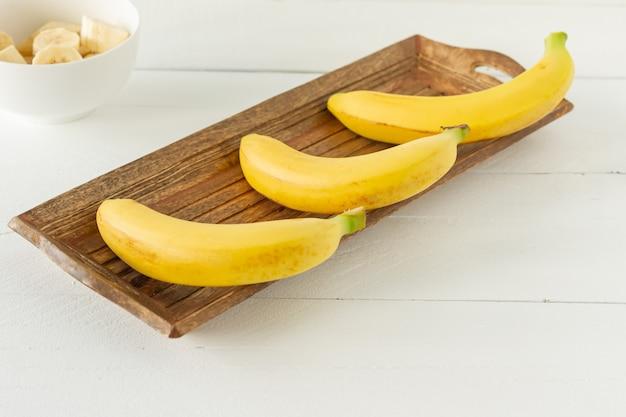 Reife bananen auf holzhintergrund. leckere gesunde tropische früchte.