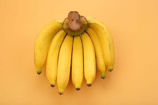 Reife bananen auf orange pastellhintergrund