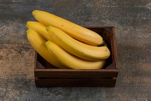 Reife bananen in der schachtel auf der marmoroberfläche