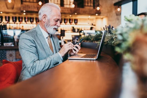 Reife bartgeschäftsleute, die im modernen café am laptop arbeiten.