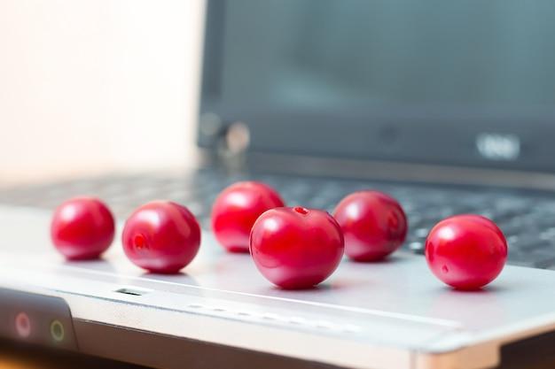 Reife beeren auf einem laptop. essenspause während der arbeit im büro. nützliches und leckeres essen. vitamine für die gesundheit