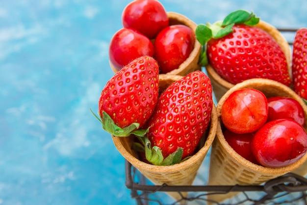 Reife bio-erdbeeren, glänzende süßkirschen in waffel-eistüten im korb
