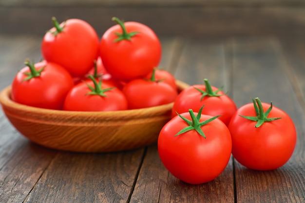 Reife bio-tomaten in einer holzschale auf einem rustikalen tisch.