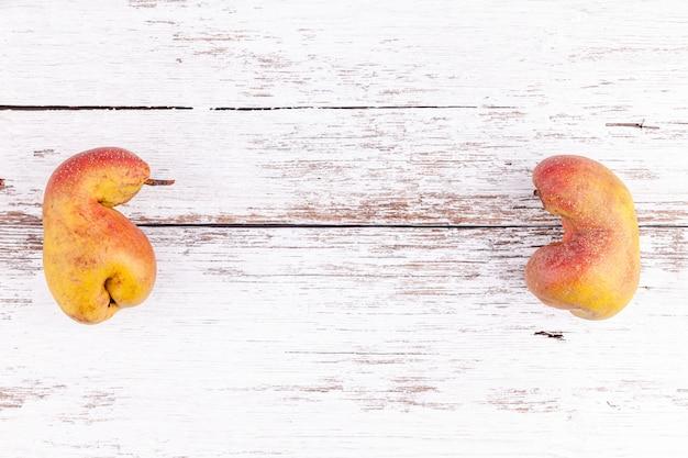 Reife birnen der hässlichen organischen früchte auf weißem holztischhintergrund mit kopienraum