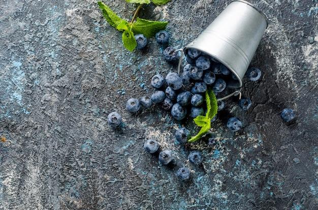 Reife blaubeeren im mini-eimer mit blattminze auf dunklem betonhintergrund