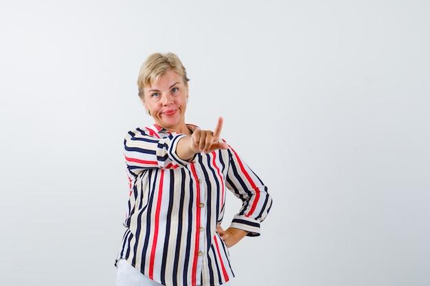 Reife blonde frau in einem vertikal gestreiften hemd