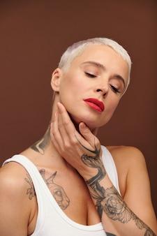 Reife blonde frau mit tätowierungen am arm, die ihr gesicht mit der hand berührt und ihre augen geschlossen hält