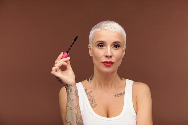Reife blonde frau mit tätowierungen an armen und brust und rotem lippenstift auf den lippen, die schwarze wimperntusche halten, während sie sie auf die wimpern auftragen