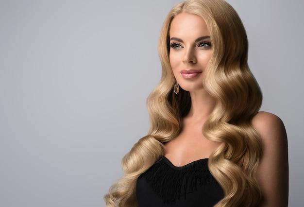 Reife blonde frau mit voluminösen locken, ausgezeichneten haarwellen. wunderschönes modell mit langem, dichtem, krausem haar und zartem make-up mit rosenlippenstift. friseurkunst, haarpflege und make-up.