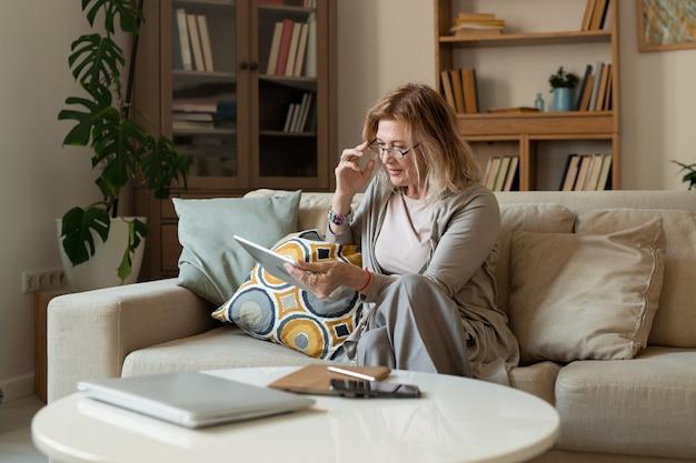 Reife blonde geschäftsfrau in freizeitkleidung und brille sitzt auf der couch im wohnzimmer und blättert durch online-nachrichten