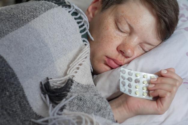 Reife brünette frau, die im bett unter karierter decke, konzept der krankheit oder kälte, behandlung zu hause, selektiver fokus schläft