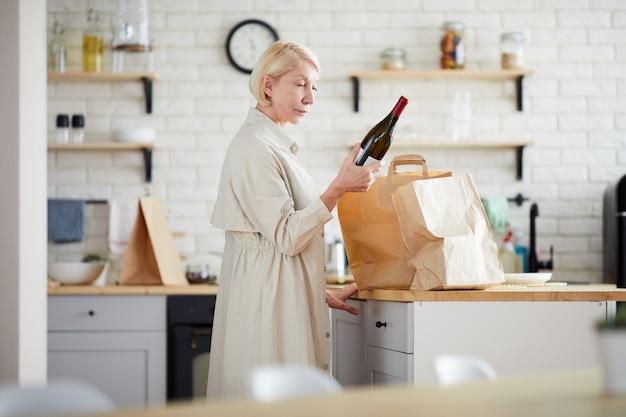 Reife dame, die papiertüten in der küche auspackt