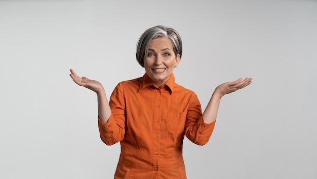 Reife dame in der orangefarbenen bluse, die hände mit geöffneten handflächen hebt
