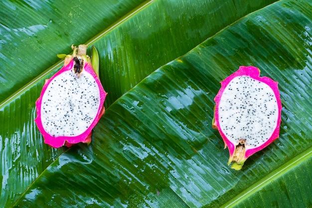 Reife drachenfrucht auf einem nassen grünen blatt. vitamine, obst, gesunde lebensmittel