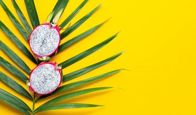 Reife drachenfrucht oder pitahaya auf tropischen palmblättern. draufsicht