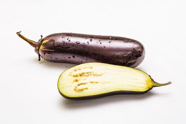 Reife einzelne aubergine. frisches ganzes und halbes gemüse.