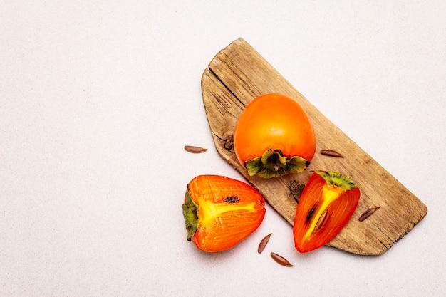 Reife einzelne persimone. frisches ganzes obst, halb geschnitten, samen. holzschneidebrett,
