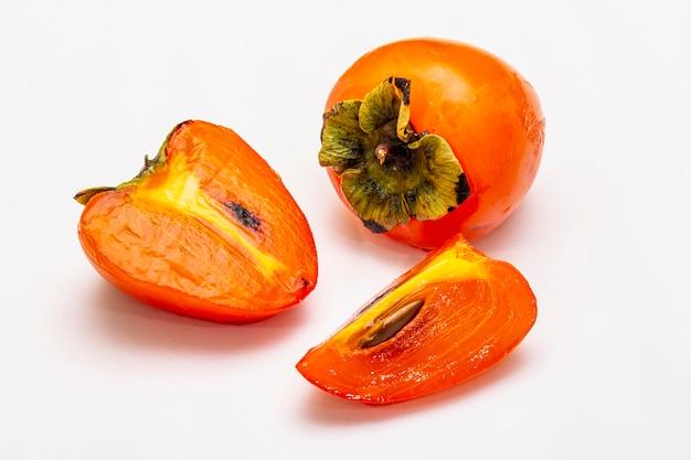 Reife einzelne persimone. frisches ganzes obst, halb geschnitten, samen.