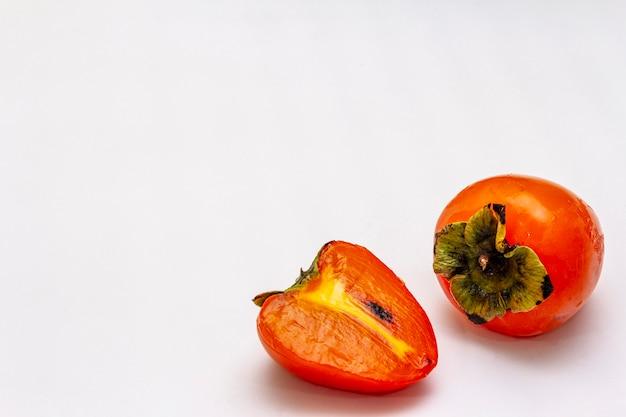 Reife einzelne persimone. frisches ganzes obst, halb geschnitten.