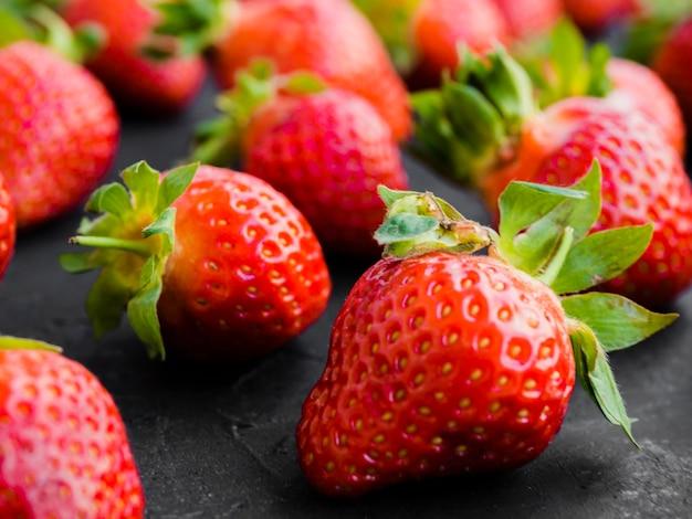 Reife erdbeere auf schwarzer oberfläche