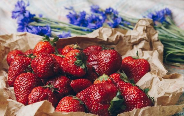 Reife erdbeere mit blumen in der papierverpackungsnahaufnahme. frische reife trawberries.