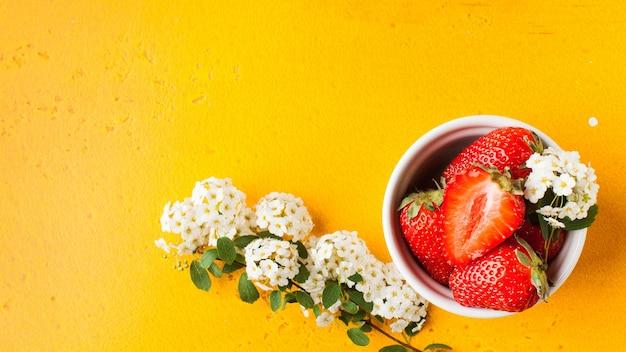 Reife erdbeeren ganz und in eine weiße schüssel auf gelb geschnitten, umgeben von weißen blumen kopieren raum