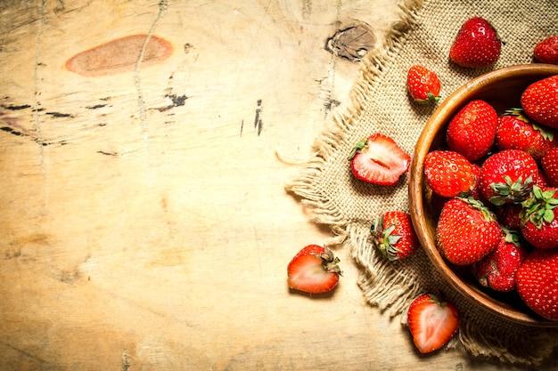 Reife erdbeeren in der schüssel auf sack auf holztisch.