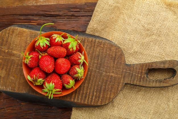 Reife erdbeeren in einem teller auf einem holztisch auf einem holzbrett.