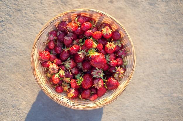 Reife erdbeeren in einem weidenkorb auf einem grauen tisch