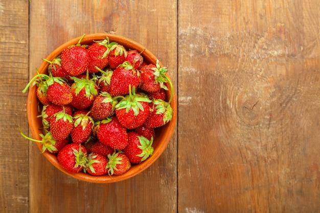 Reife erdbeeren in einem weidenkorb auf einem hölzernen hintergrund. horizontales foto