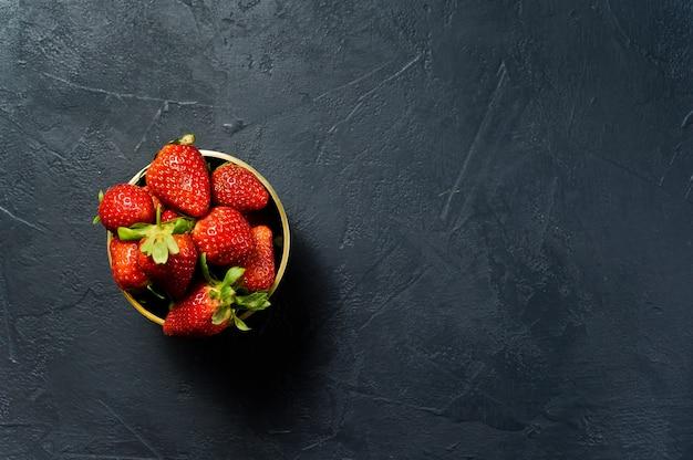 Reife erdbeeren in einer goldenen schüssel.